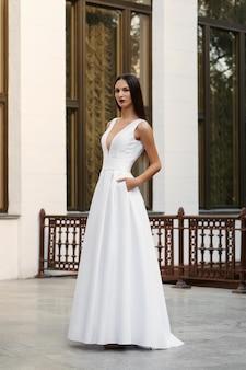 Menina bonita no vestido longo branco com um decote profundo. modelo posando no terraço de um palácio.