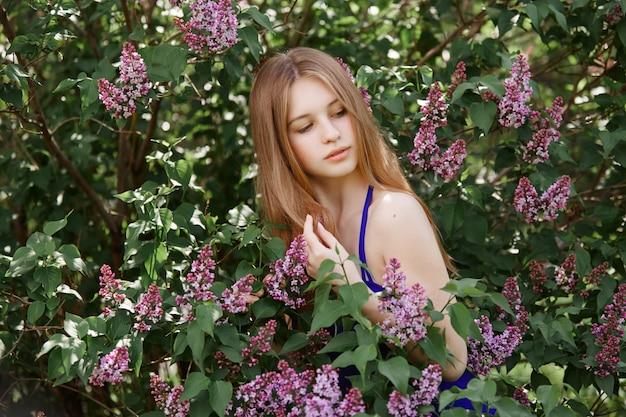 Menina bonita no vestido posando perto de arbusto de lilases