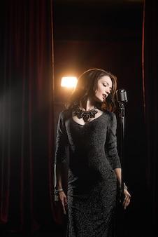 Menina bonita no vestido preto, cantando no microfone na sala de concertos