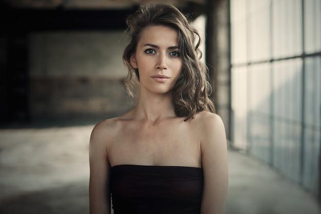 Menina bonita no vestido preto com cabelo encaracolado