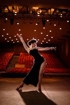 Menina bonita no vestido preto dançando contra um fundo escuro.