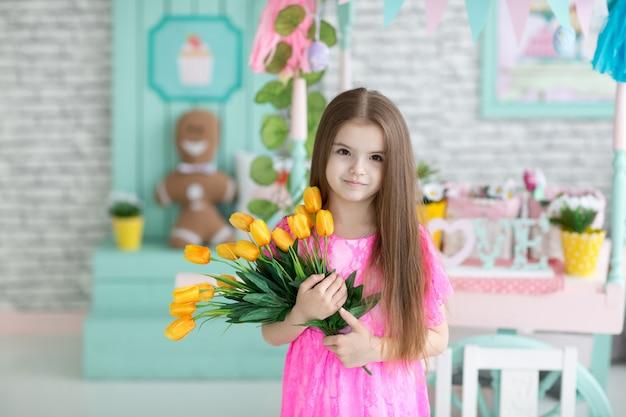 Menina bonita no vestido rosa com flores