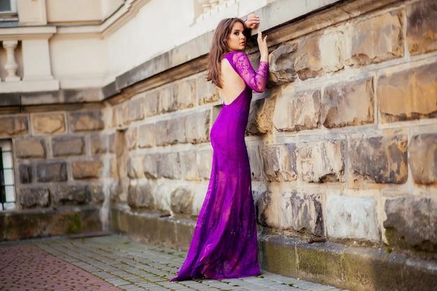 Menina bonita no vestido roxo encostado na parede