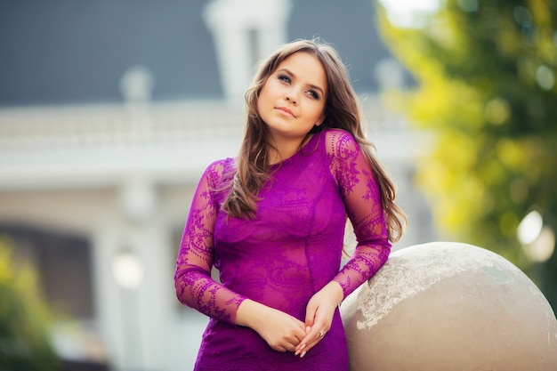 Menina bonita no vestido roxo inclinou-se na bola