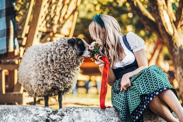 Menina bonita no vestido tradicional oktoberfest com buquê de flores, sentado perto de ovelhas bonitas na fazenda