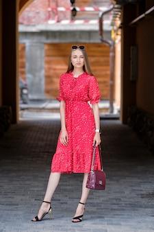 Menina bonita no vestido vermelho andando na rua na cidade velha
