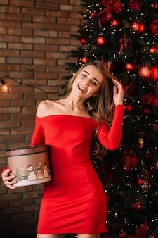 Menina bonita no vestido vermelho sexy com caixa de presentes perto da árvore de natal