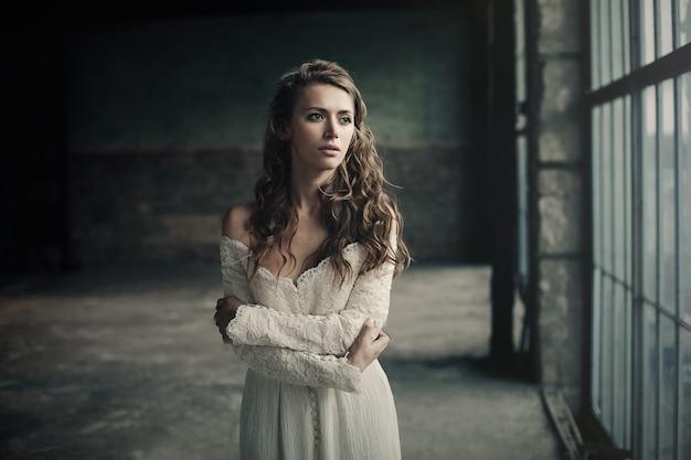 Menina bonita no vestido vintage branco com cabelo encaracolado