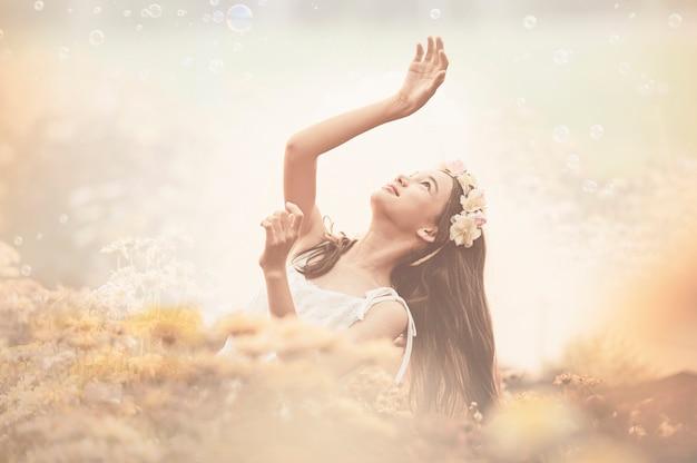 Menina bonita no vestido vintage e chapéu de pé perto de flores coloridas