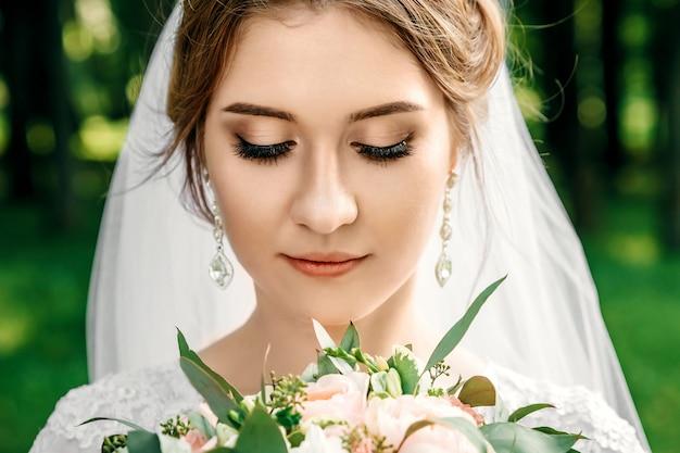 Menina bonita, noiva em um vestido de casamento branco em um fundo da natureza verde. casamento, criação familiar.
