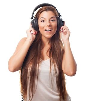 Menina bonita nos auscultadores que escuta a música