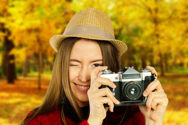 Menina bonita nova com a câmera no parque do outono