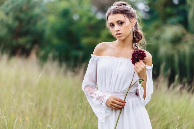 Menina bonita nova com a flor no vestido leve que anda no gramado perto da floresta do verão