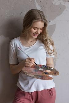 Menina bonita nova com escova que mistura cores na paleta
