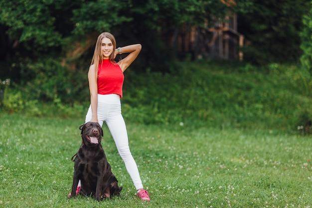 Menina bonita nova com seu cão preto labrador no parque.