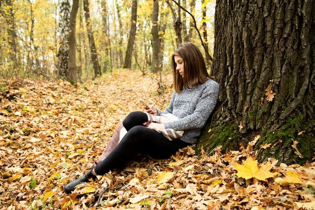 Menina bonita nova em um revestimento cinzento que senta-se na floresta do outono perto de uma grande árvore com um telefone móvel