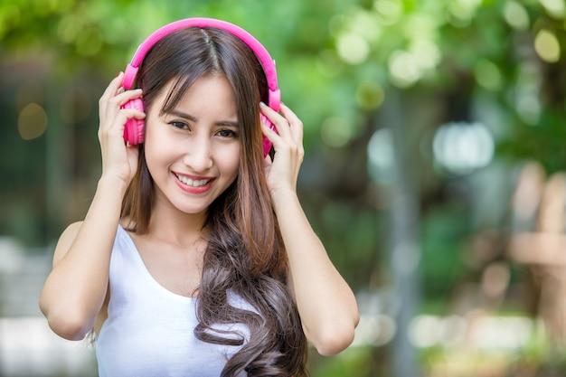 Menina bonita nova feliz que escuta a música com seus auscultadores cor-de-rosa e que dança no parque urbano