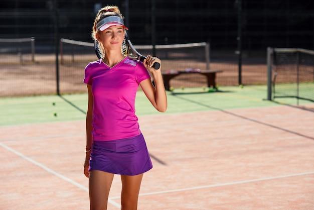Menina bonita nova no uniforme com a raquete de tênis no pé que está no campo de tênis ao ar livre moderno no por do sol. conceito de esporte e saúde.