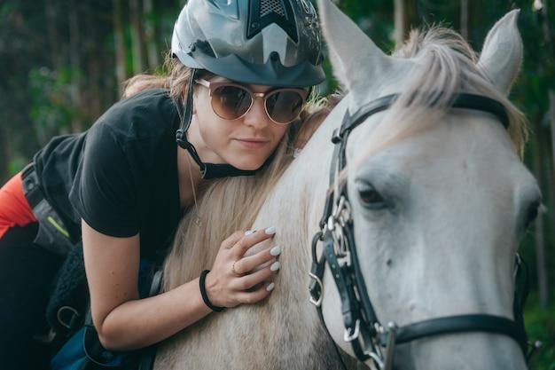 Menina bonita nova que abraça o cavalo na natureza. amante de cavalo.