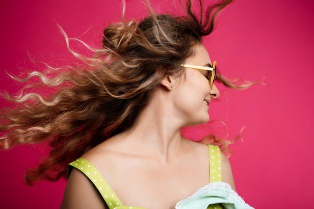 Menina bonita nova que acena a cabeça sobre a parede cor-de-rosa.