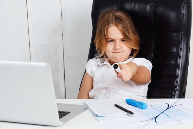 Menina bonita nova que aponta a pena de feltro à câmera no escritório.