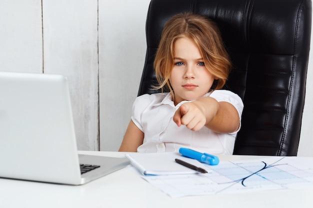Menina bonita nova que aponta o dedo à câmera no escritório.