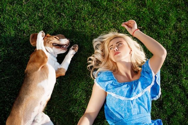 Menina bonita nova que encontra-se com o cão do lebreiro na grama no parque.