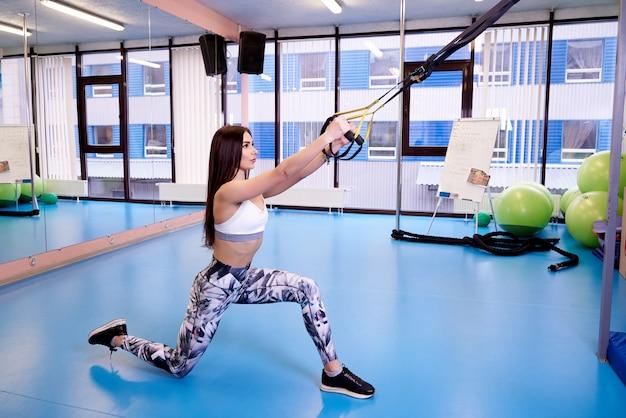 Menina bonita nova que exercita com as correias da aptidão no gym.