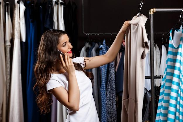 Menina bonita nova que fala no telefone no shopping.