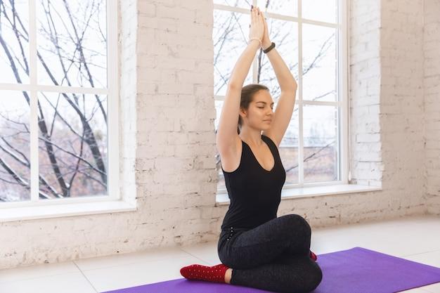 Menina bonita nova que faz o asana do gomukhasana da ioga. mãos para cima, vista frontal