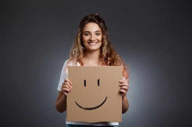 Menina bonita nova que guarda a caixa com smiley sobre a parede cinzenta.