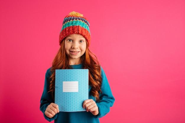 Menina bonita nova que mostra o livro azul da cópia e o sorriso isolado