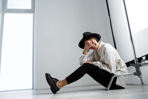 Menina bonita nova que ri sentado no assoalho sobre a parede branca.