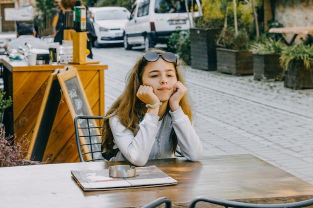 Menina bonita nova que senta-se em um café da rua na cidade velha de antalya