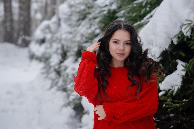Menina bonita nova que veste a camisola vermelha no parque do inverno. conceito saudável da vida e da beleza. garota se divertindo conceito. copyspace horizontal
