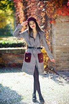 Menina bonita nova que veste o casaco e o tampão do inverno no fundo das folhas de outono.