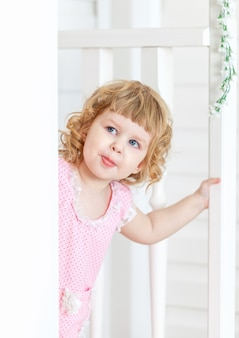 Menina bonita olha para a rua e sorrindo por trás da porta