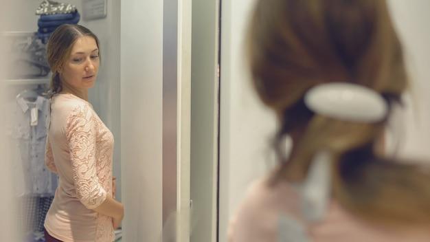 Menina bonita olha para seu reflexo no espelho enquanto experimenta roupas em uma loja de moda