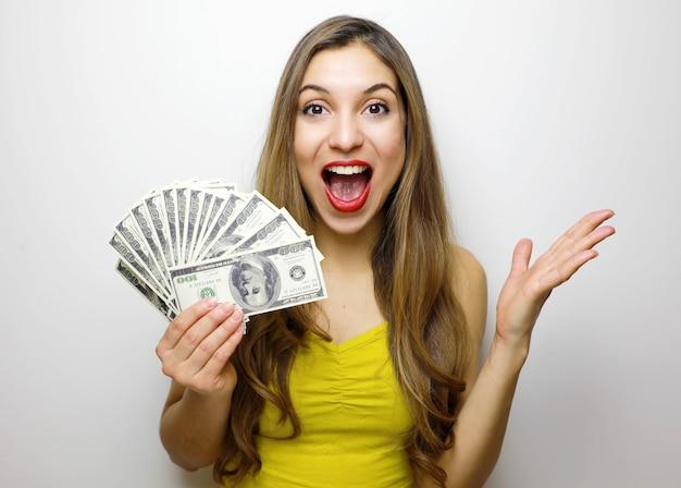 Menina bonita olhando para a câmera com um monte de notas de dinheiro