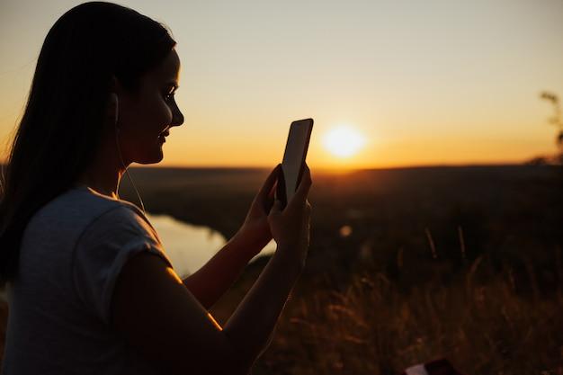 Menina bonita olhando para o telefone ao pôr do sol. imagem de close-up de menina segurando o smartphone no fundo por do sol.