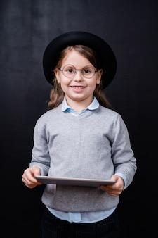 Menina bonita olhando para você com um sorriso cheio de dentes enquanto usa o touchpad na frente da câmera contra o espaço preto