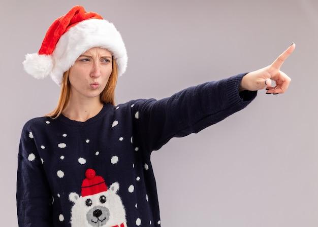Menina bonita olhando preocupada com chapéu de natal apontando para o lado isolado no fundo branco