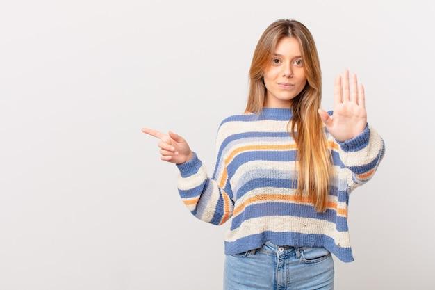 Menina bonita olhando séria mostrando a palma da mão aberta fazendo gesto de pare