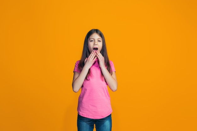 Menina bonita olhando surpreso isolado na parede laranja