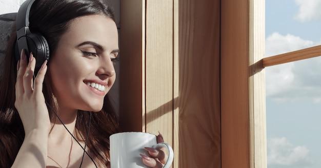 Menina bonita, ouvindo música em fones de ouvido e tomando café enquanto está sentado no peitoril da janela e sorrindo