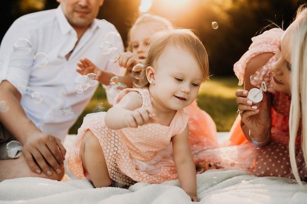 Menina bonita pegando bolhas de sabão sorrindo. criança adorável brincando com os pais e a irmã lá fora contra o pôr do sol.