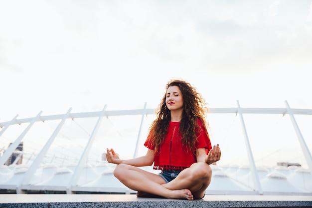 Menina bonita pensativa tentando se acalmar, sentado em posição de lótus na laje de mármore