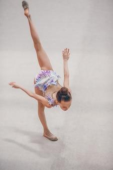 Menina bonita pequena ginasta ativa com seu desempenho no tapete