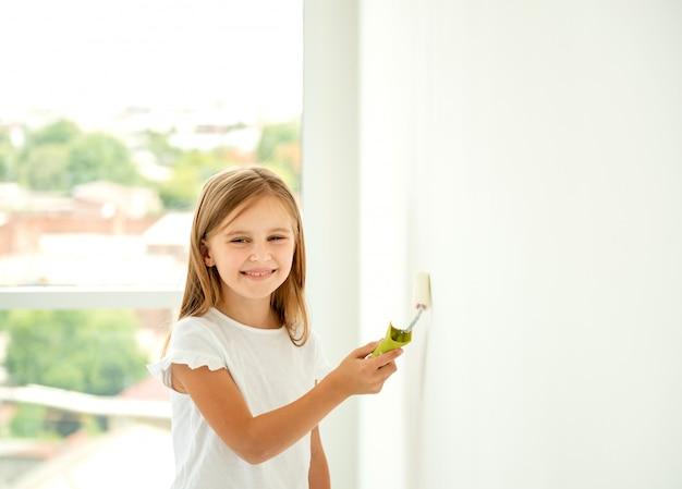 Menina bonita pinta uma parede com rolo de pintura