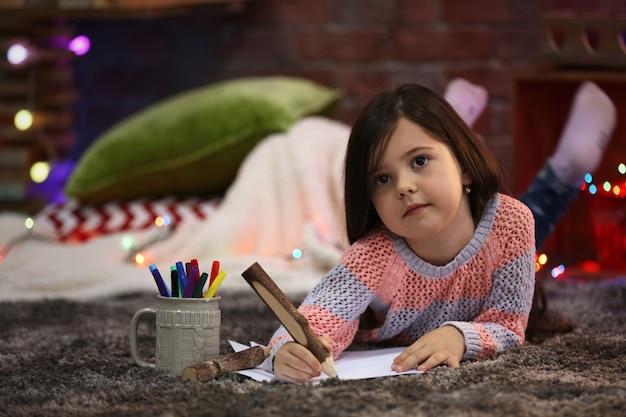 Menina bonita pintando em um quarto decorado de natal